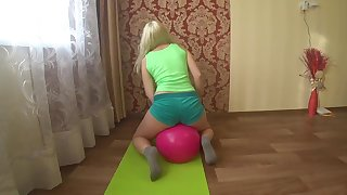 Lesbian in tight shorts on a big ass is engaged in fitness and horny and her friend with a dildo fucks her hairy pussy.